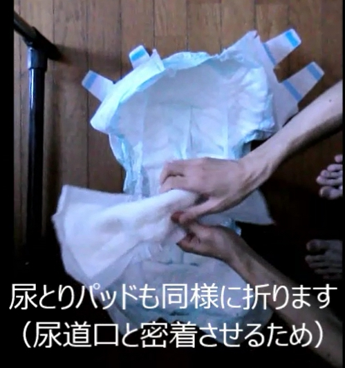 尿とりパッドを折って、おむつのギャザーの内側にセット